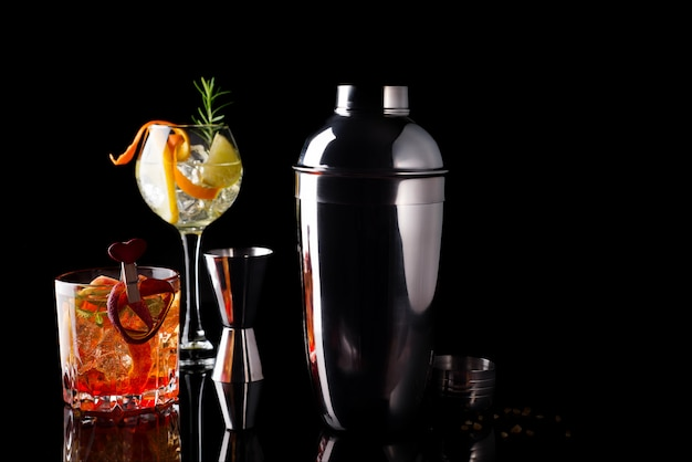 Różne koktajle w szklanych kieliszkach z akcesoriami bar