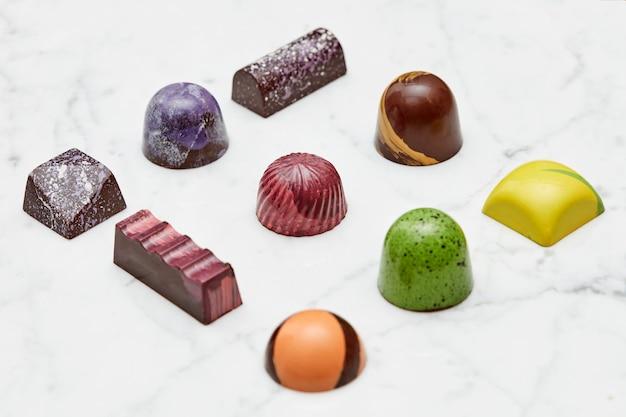 Różne kolekcja czekoladowych cukierków i słodyczy, izolowana na białym marmurowym tle