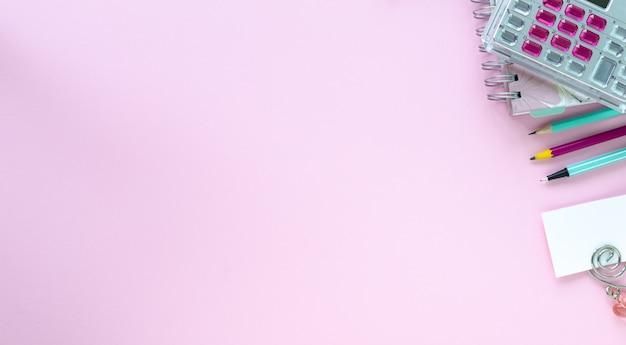 Różne kolorowe artykuły papiernicze do szkoły i biura na różowym tle z copyspace.