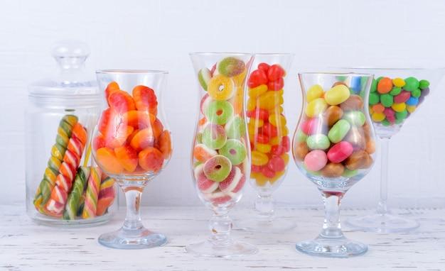 Różne kolorowe cukierki owocowe w okularach na stole na jasnym tle