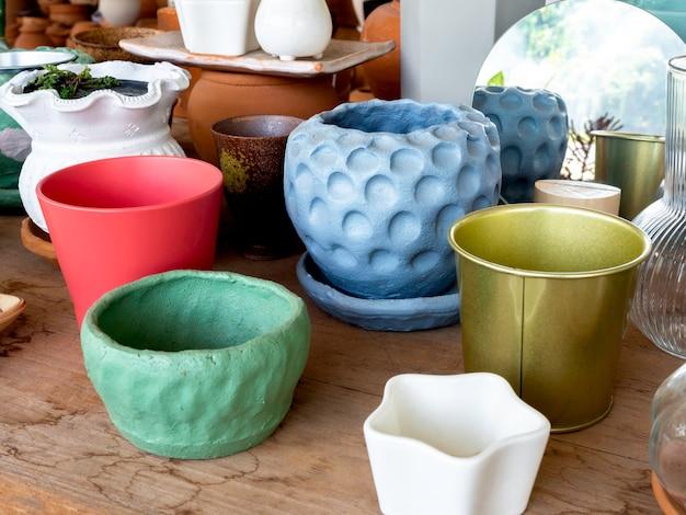 Różne kolorowe doniczki ceramiczne na drewnianym stole w sklepie. pusta geometryczna doniczka ceramiczna diy.