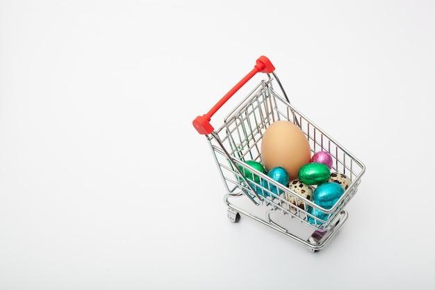Różne kolorowe jaja kurze znajdują się w wózku spożywczym na białym tle
