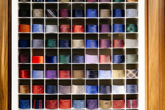 Różne kolorowe krawaty starannie złożone w rzędzie