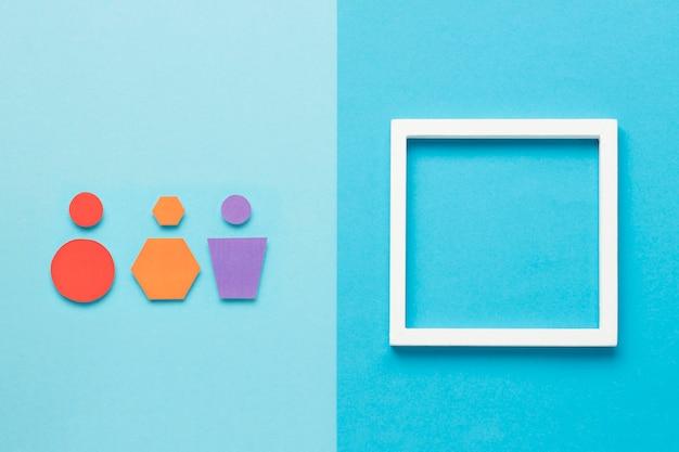Różne kolorowe kształty geometryczne obok pustej ramki