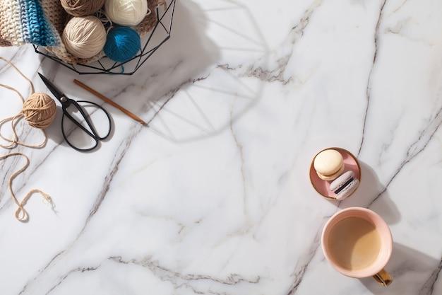 Różne kolorowe kulki przędzy wełnianej filiżanka kawy z makaronikiem