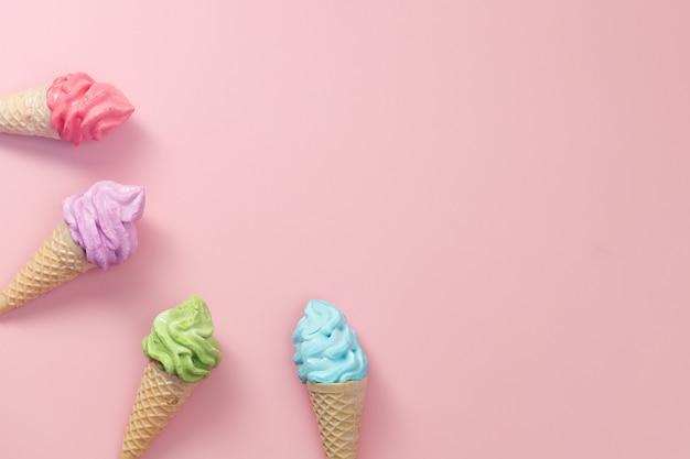Różne kolorowe lody bezowe na różowym tle dla słodkiej i orzeźwiającej koncepcji deserowej