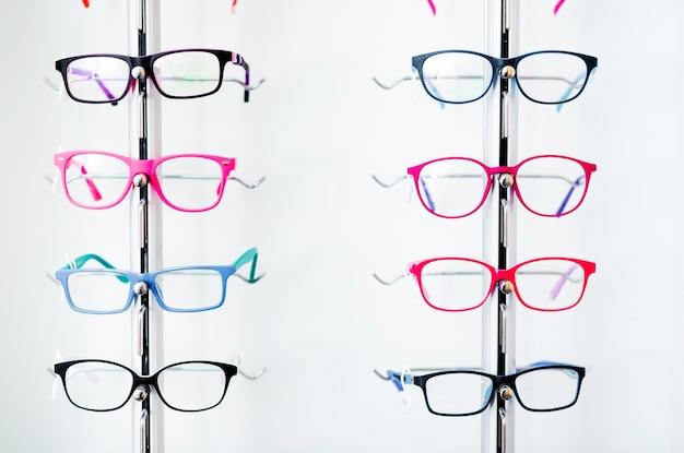 Różne kolorowe okulary do rodzajów na gablocie w sklepie optycznym