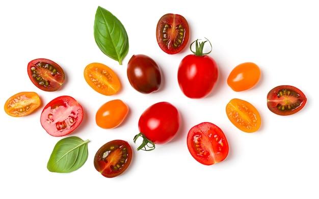 Różne kolorowe pomidory i liście bazylii na białym tle.