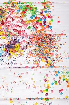 Różne kolorowe posypki rozrzucone na białym drewnianym stole