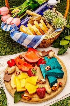 Różne kolorowe serki i kosz z chlebem, winem i sokiem truskawkowym na sztucznej zielonej trawie