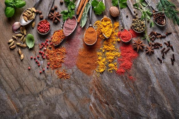 Różne kolorowe zioła i przyprawy w łyżkach do gotowania: kurkuma, koperek, papryka, cynamon, szafran, bazylia i rozmaryn. indyjskie przyprawy. na starym kamiennym brązowym tle. widok z góry.