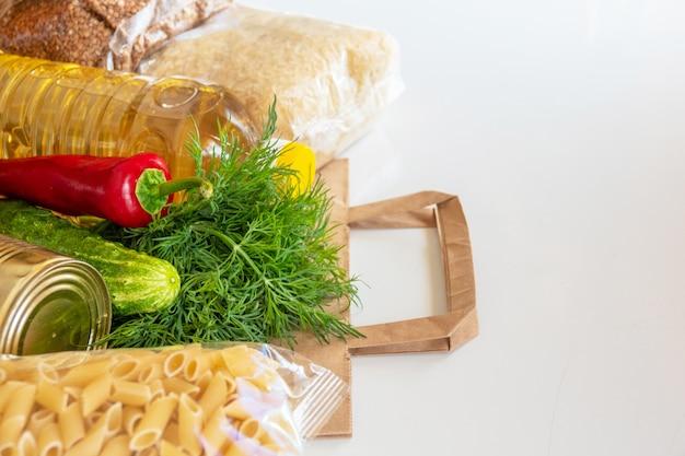 Różne konserwy, makarony i płatki zbożowe w tekturowym pudełku. darowizny żywności lub koncepcja dostawy żywności.