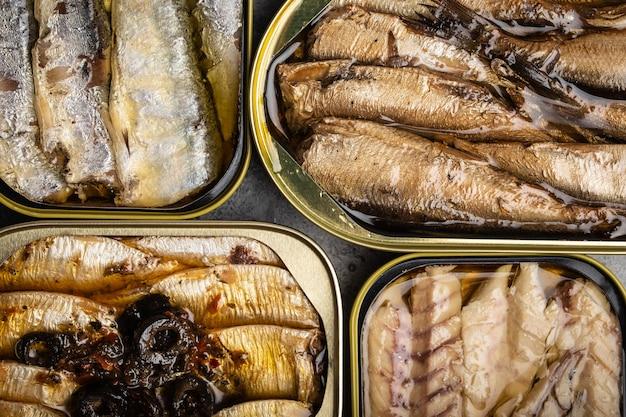 Różne konserwy rybne w puszce na szarym betonowym tle: sardynka, wędzona sardynka, makrela. ryby w puszce jako wygodny, szybki i zdrowy pokarm oraz źródło kwasów tłuszczowych omega-3, białka i witaminy d