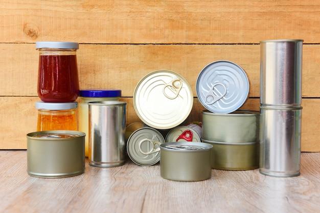 Różne konserwy w metalowych puszkach na drewnianym stole - konserwy niepsujące się artykuły spożywcze w kuchni w domu lub na datki