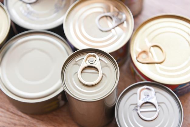 Różne konserwy w metalowych puszkach na drewnianym tle, widok z góry konserwy nietrwałe produkty do przechowywania żywności w kuchni w domu lub na datki