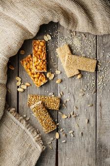 Różne kozinaki ,, z tkaniną jutową. stylu country. pyszne słodycze z nasion słonecznika, sezamu i orzeszków ziemnych, pokryte błyszczącą polewą.