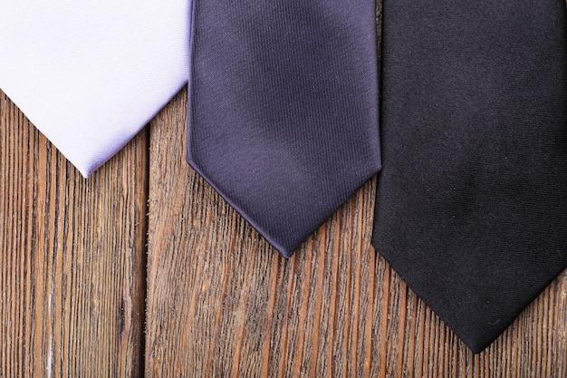 Różne krawaty na drewnianych deskach