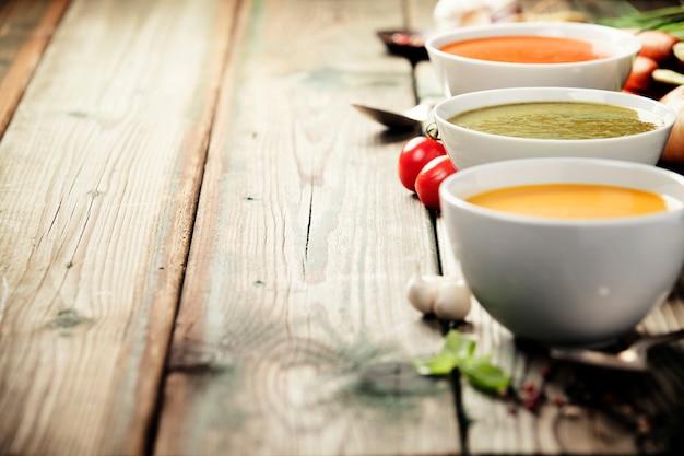 Różne kremowe zupy na starym drewnianym stole