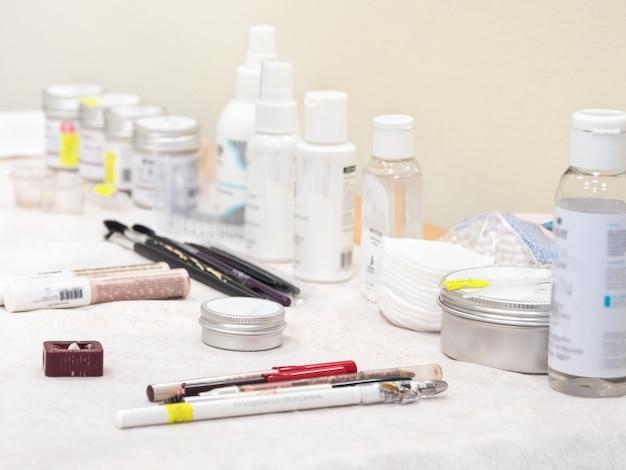 Różne kremy i produkty do barwienia brwi są na stole w salonie piękności, nieostrość.
