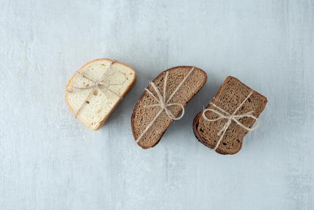 Różne kromki chleba związane sznurem.
