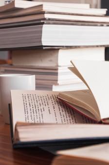 Różne książki w pobliżu kubka