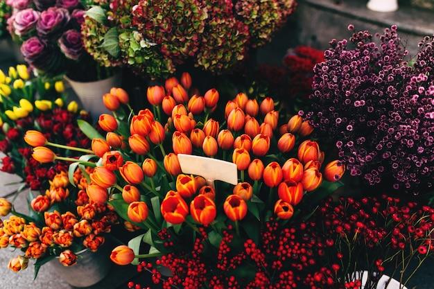 Różne kwiaty w oknie wystawowym sklepu z pustymi metkami z cenami