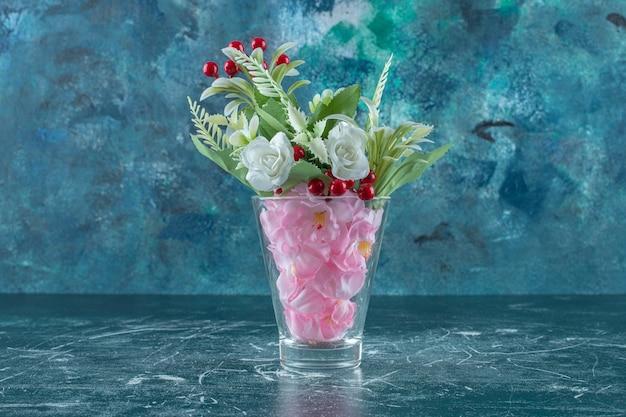 Różne kwiaty w szklance, na niebieskim tle.