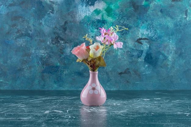 Różne kwiaty w wazonie na niebieskim stole.