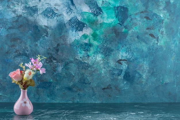 Różne kwiaty w wazonie, na niebieskim tle.