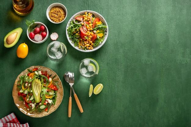 Różne letnie zdrowe sałatki warzywne z awokado, ogórkiem, rzodkiewką, papryką i pomidorem na zielonym tle. zdrowa żywność.widok z góry.