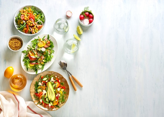 Różne letnie zdrowe sałatki warzywne z awokado, ogórkiem, rzodkiewką, papryką i pomidorem. zdrowa żywność.widok z góry.