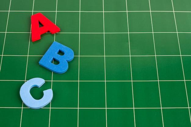 Różne litery leżą na zielonej powierzchni tablicy