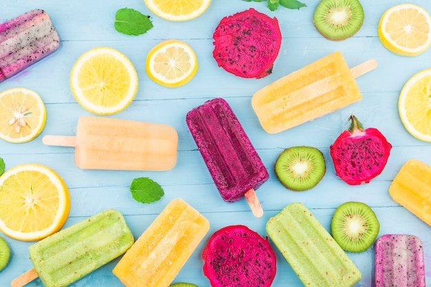Różne lody owocowe są umieszczane na niebieskim tle drewnianej deski, lody kiwi, lody pomarańczowe, lody owocowe smoka, lody kantalupa