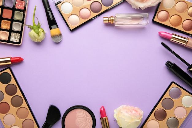 Różne luksusowe produkty do makijażu na fioletowym tle, leżał płasko. widok z góry