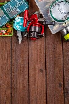 Różne macki wędkarskie z przynętami i kołowrotkami na drewnianym brązowym tle z miejscem na tekst. projekt do reklamy i publikacji.