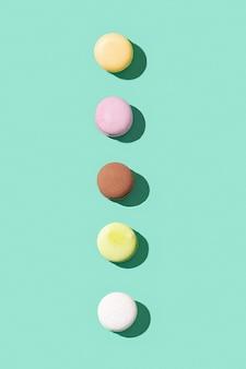 Różne makaroniki na jasnoniebiesko-zielonych kolorowych francuskich ciasteczkach macarons