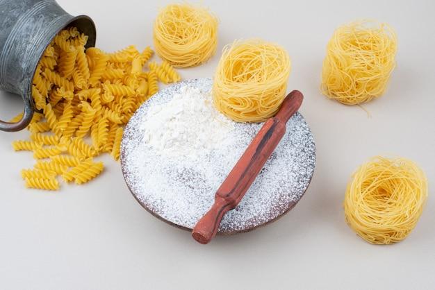 Różne makarony i mąka na surowo z wałkiem do ciasta.
