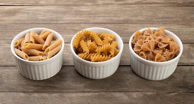 Różne makarony pełnoziarniste na miski na drewnianym stole.