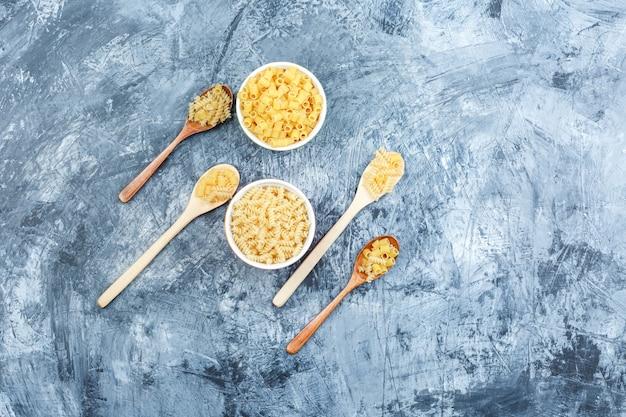 Różne makarony w drewniane łyżki i miski na tle nieczysty tynk. widok z góry.