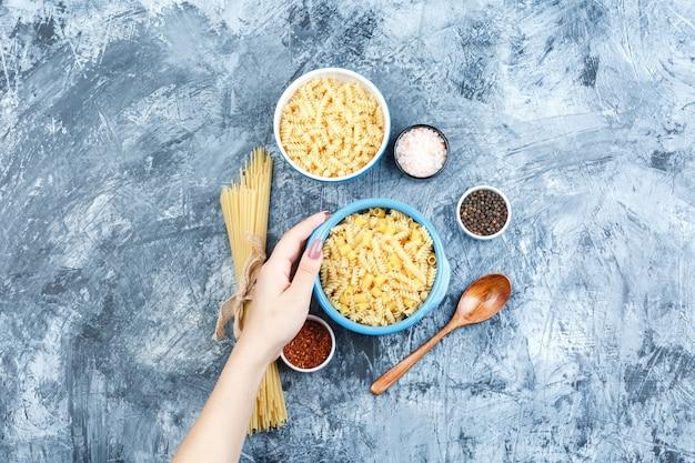 Różne makarony w miski i ręka trzyma miskę makaronu z przyprawami, widok z góry drewnianą łyżką na szarym tle tynku