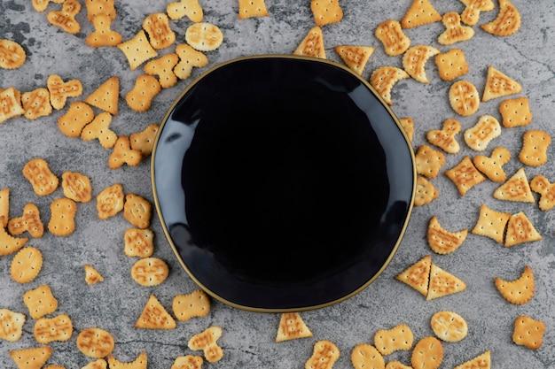Różne małe krakersy rozrzucone w pobliżu czarnej płyty na marmurowym tle.