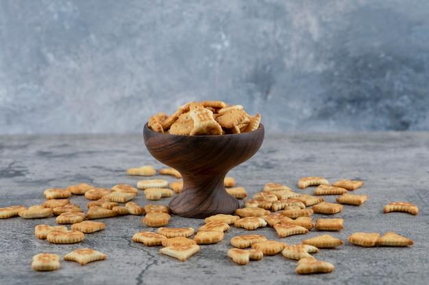 Różne małe krakersy w drewnianej misce i rozrzucone na marmurowym tle.