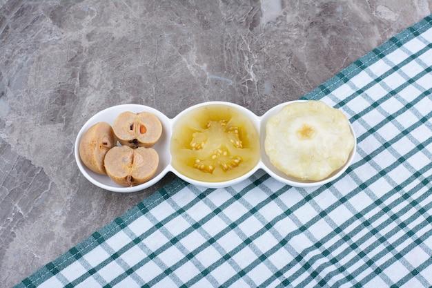 Różne marynowane warzywa i owoce w miseczkach z obrusem.