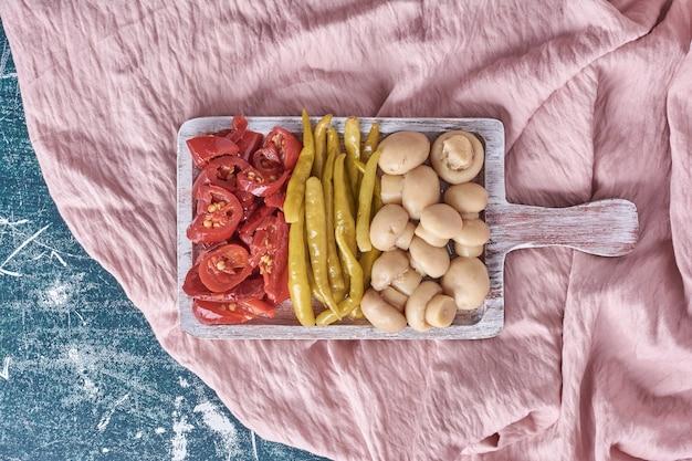Różne marynowane warzywa na białym talerzu z obrusem.