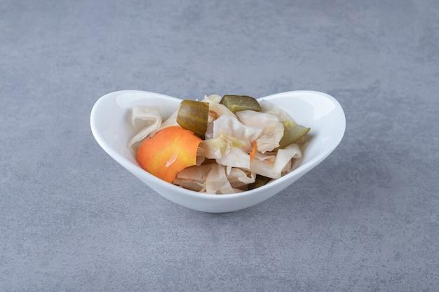 Różne marynowane warzywa w misce, na marmurowym tle.