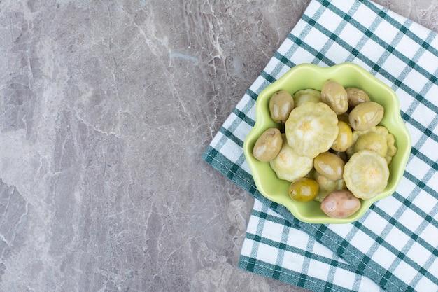 Różne marynowane warzywa w misce z obrusem.