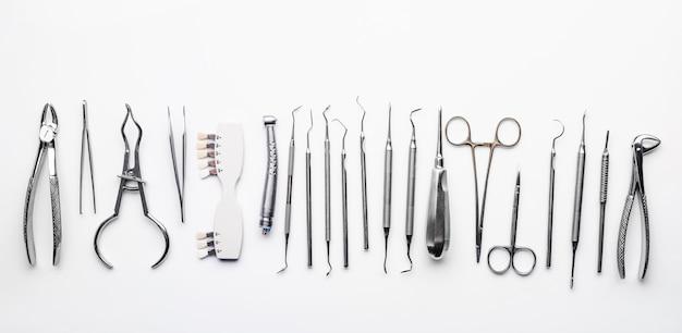 Różne metalowe narzędzia dentystyczne na białym stole