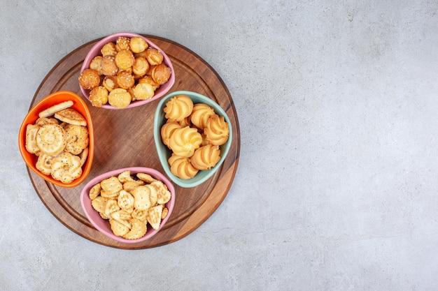 Różne miski kruchych ciastek i chipsów na drewnianej desce na marmurowej powierzchni