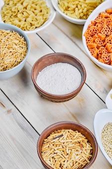 Różne miski surowego makaronu i mąki na drewnianym stole.