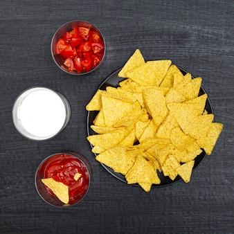 Różne miski z pomidorami nachos czerwonymi i białymi sosami